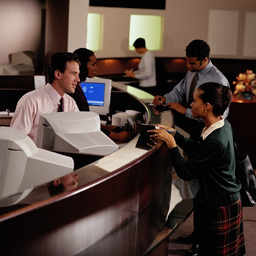 A lady at the counter talking to a bank teller
