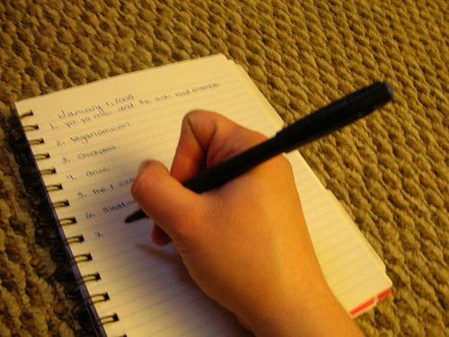 hand with pen, writing a list