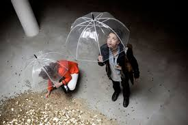 Woman and child hold umbrellas, as coins rain down.