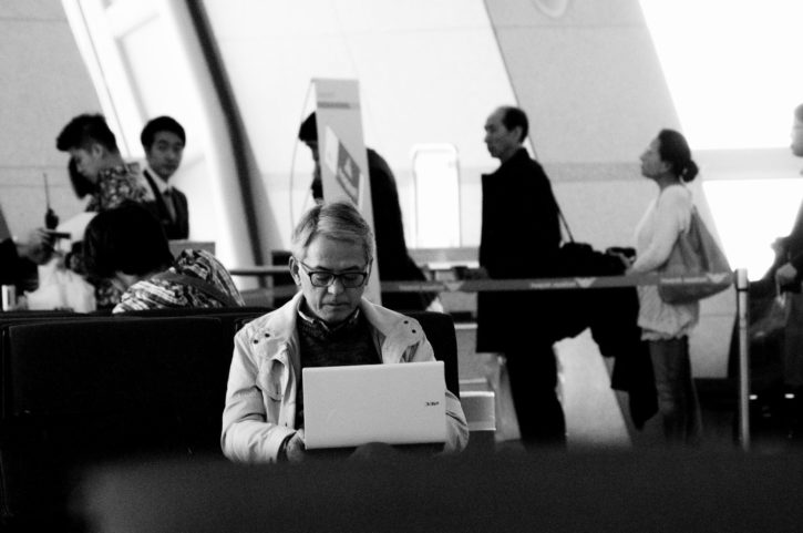 crowd at an airport, man works on laptop