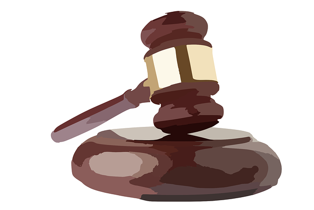 Auctioneer's gavel or hammer hovers above the block.